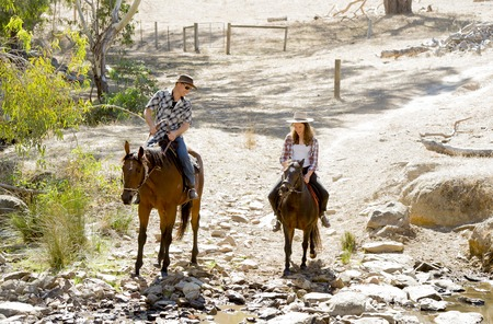 young American Australian man as father or horse instructor of young girl or  teen daughter riding little pony wearing cowgirl hat in countryside Summer vacation ride Stock Photo