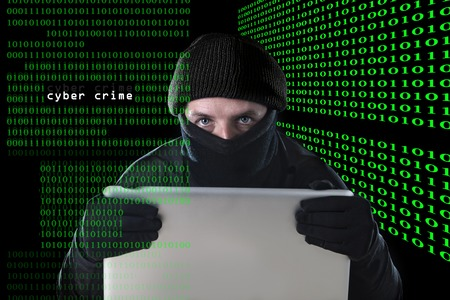 criminal activity: hacker man in black using computer laptop for criminal activity hacking password and private information cracking password too access bank account data in cyber crime concept Stock Photo