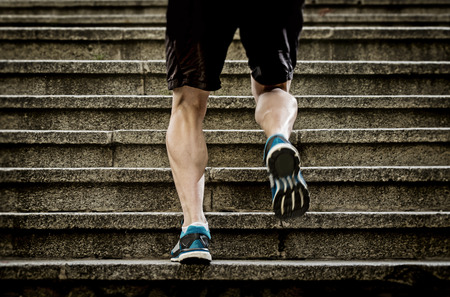 workout: athletic legs of young sport man with sharp scarf muscles running on staircase steps jogging in urban training workout or runner competition in fitness and healthy lifestyle concept