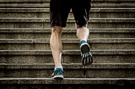 escalera: piernas atléticas de joven deportiva con músculos bufanda afilados que se ejecuta en pasos de escalera trotar en sesión de entrenamiento o competición corredor urbano en la aptitud y el concepto de estilo de vida saludable