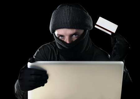 criminal activity: man in black holding credit card using computer laptop for criminal activity hacking password and private information cracking password too access bank account data in cyber crime concept