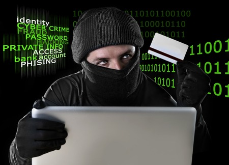 private data: man in black holding credit card using computer laptop for criminal activity hacking password and private information cracking password too access bank account data in cyber crime concept