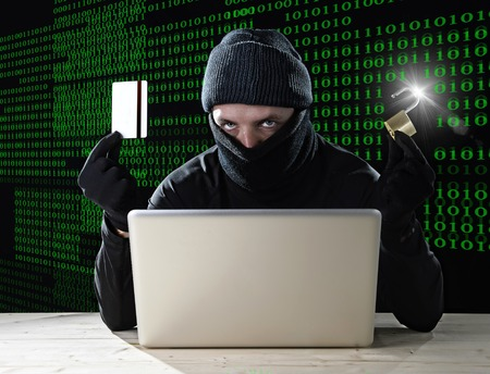 private access: man in black holding credit card and lock using computer laptop for criminal activity hacking bank account password and private information cracking password for illegal access in cyber crime concept