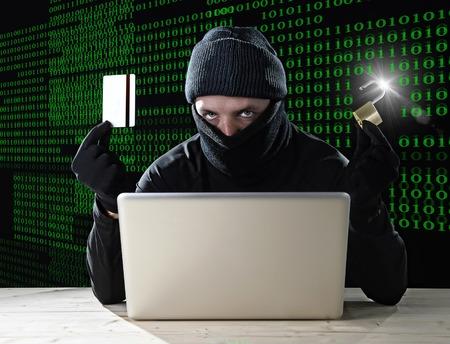 man in het zwart bedrijf creditcard en slot laptop computer met behulp van criminele activiteiten hacken bankrekening wachtwoord en prive-informatie kraken wachtwoord voor illegale toegang in cyber-concept misdaad Stockfoto