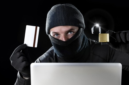 man in black holding credit card and lock using computer laptop for criminal activity hacking bank account password and private information cracking password for illegal access in cyber crime concept photo