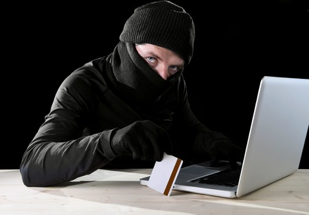 man in black holding credit card using computer laptop for criminal activity hacking password and private information cracking password too access bank account data in cyber crime concept photo