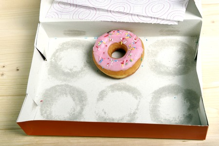empty cakes box with only one tempting and delicious donut with toppings left in unhealthy nutrition and sugar and sweet cake addiction concept Foto de archivo