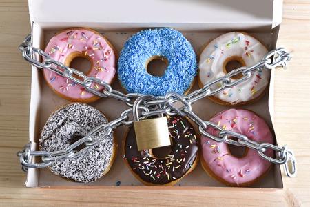 doos vol verleidelijke heerlijke donuts verpakt in metalen ketting en slot in suiker en zoete verslaving en voeding lichaam en tandheelkundige zorg concept