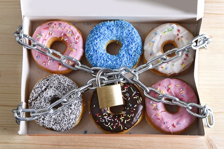 box full of tempting delicious donuts wrapped in metal chain and lock in sugar and sweet addiction and diet body and dental care concept Archivio Fotografico