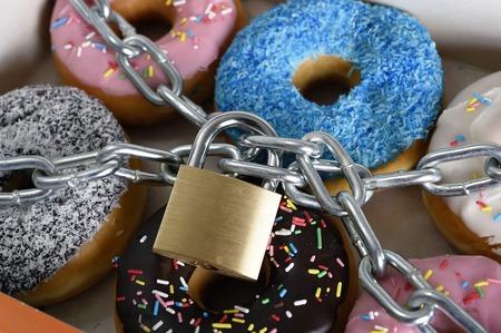 comida chatarra: caja llena de deliciosos donuts tentadoras envueltos en cadena de metal y bloquear en el azúcar y la adicción dulce y cuerpo dieta y el concepto de atención dental