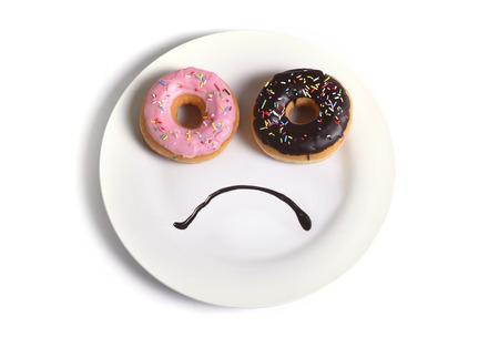 Smiley droevig gezicht zorgen over overgewicht gemaakt op schotel met donuts als ogen en chocolade siroop als mond suiker en zoete verslaving, dieet en voeding concept op een witte achtergrond Stockfoto - 40416419