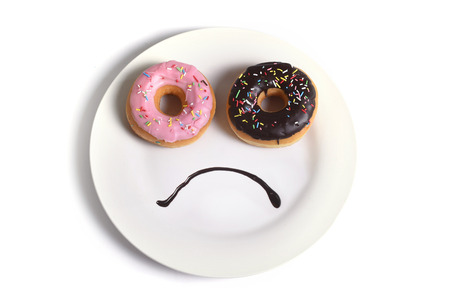 smiley sad face worried about overweight made on dish with donuts as eyes and chocolate syrup as mouth in sugar and sweet addiction , diet and nutrition concept isolated on white background Stock Photo