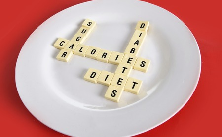 dieting: crossword game on dish on table red mat with words sugar , calories, diabetes and diet taking in sugar abuse health risk , dieting and healthy nutrition concept Stock Photo