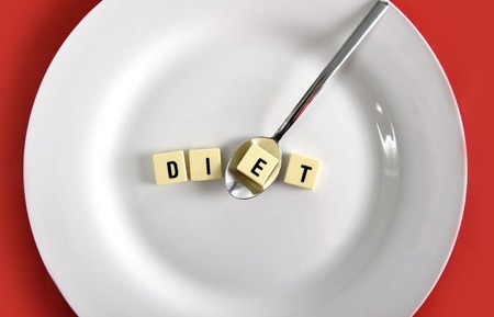 excess: diet block word in crossword with spoon on dish on table red mat taking one letter in sugar excess, dieting and healthy nutrition concept