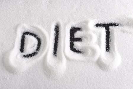 dieting: diet word written with finger on pile of sugar in dieting and healthy nutrition concept isolated on white grainy sweet background