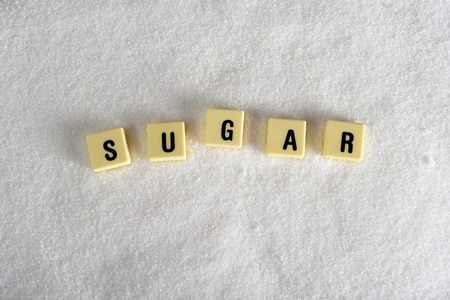 overuse: sugar block letters in crossword over sugar pile isolated on grainy white sugar texture in sweet food abuse, dieting and healthy nutrition concept