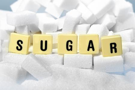 azucar: letras de molde el az�car de la palabra en la pila de cubos de az�car de cerca en la adicci�n, la nutrici�n dulce, una alimentaci�n poco saludable y el concepto de dieta