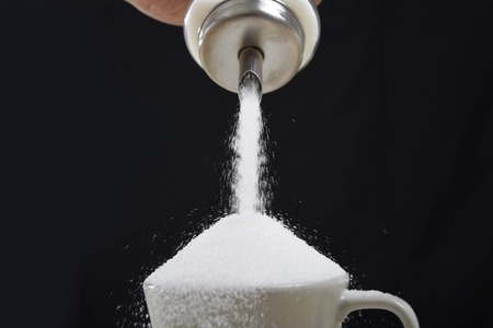 man hand with sugar bowl pouring a crazy lot of it spilling out everywhere in full coffee cup in insane sugar addiction and unhealthy nutrition concept isolated on black background