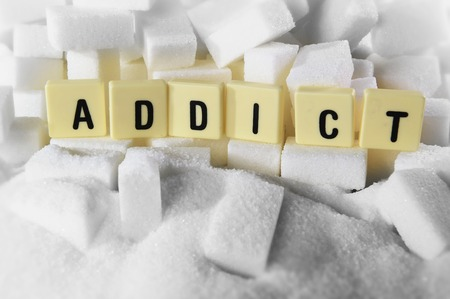 addict block letters word on pile of sugar cubes close up in sugar addiction , sweet nutrition , unhealthy eating and diet concept
