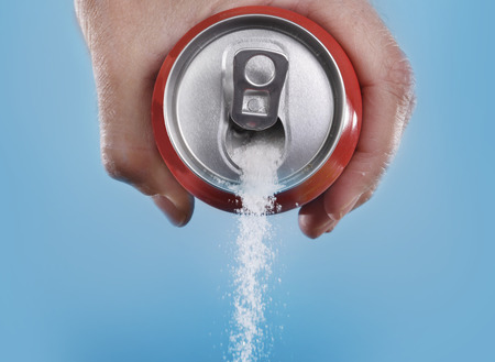 cans: hand holding soda can pouring a crazy amount of sugar in metaphor of sugar content of a refresh drink isolated on blue background in healthy nutrition, diet and sweet addiction concept Stock Photo