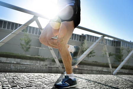 flare up: close up legs and shoes of young athletic man practicing running in urban background natural rising backlight sun and flare in fitness , body care, sport training and healthy lifestyle concept