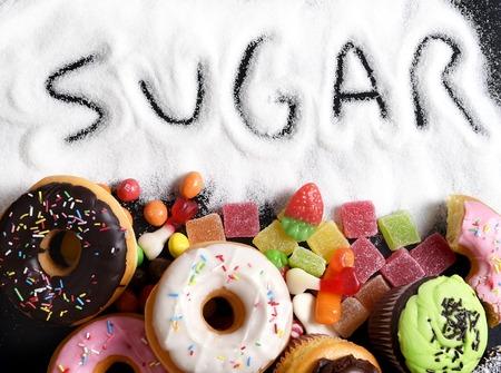 azucar: Mezcla de dulces pasteles, rosquillas y dulces con la extensión de azúcar y el texto escrito en la alimentación poco saludable, el abuso de chocolate y concepto de adicción, el cuerpo y el cuidado dental