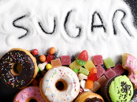 unhealthy diet: mix of sweet cakes, donuts and candy with sugar spread and written text in unhealthy nutrition, chocolate abuse and addiction concept, body and dental care