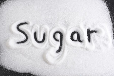 word written with finger on pile of sugar in diet , sweet overuse and healthy nutrition concept isolated on white grainy background