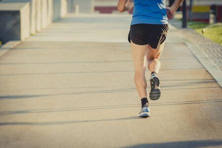 hombre fuerte: vista posterior de las piernas y los zapatos de hombre atl�tico joven que practica el funcionamiento en segundo plano urbano de entrenamiento de la aptitud del verano que representa el cuidado del cuerpo, entrenamiento deportivo y el concepto de estilo de vida saludable