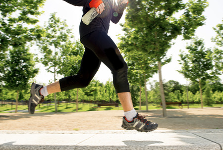 isotonic: close up  legs of young man holding isotonic energy drink while running in city park with trees on the background on summer training session fitness and healthy lifestyle concept Stock Photo