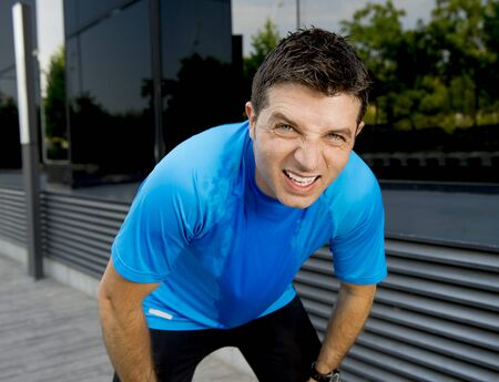 young attractive man leaning exhausted after running session sweating taking a break to recover in urban street summer background Stock Photo