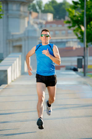 summer sport: young athletic man with sunglasses practicing running on urban city park background in summer sport training session, body and health care and healthy lifestyle concept Stock Photo