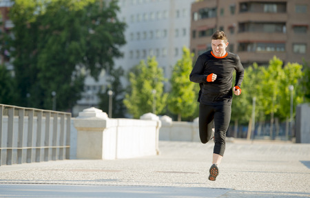 summer sport: young athletic man practicing running on urban city park background in summer sport training session, body and health care and healthy lifestyle concept