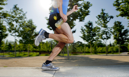 isotonic: close up athletic legs of young man holding isotonic energy drink while running in city park with trees on the background on summer training session fitness and healthy lifestyle concept