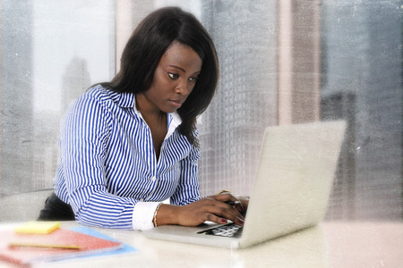 career: young attractive and efficient black ethnicity woman sitting at business district office computer laptop desk typing concentrated isolated on white background in career success concept