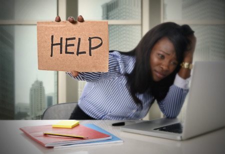 black African American ethnicity tired and frustrated woman working as secretary in stress at work business district office desk with computer laptop asking for help in frustration concept
