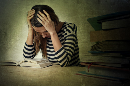 stressed: young stressed student girl studying pile of books on library desk preparing MBA test or exam in stress feeling tired and overwhelmed in youth education concept grunge messy background style Stock Photo
