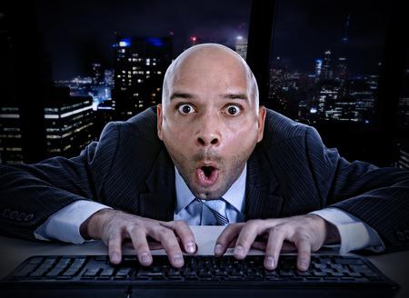 porno: giovane uomo d'affari a tarda notte in carica digitando sulla tastiera del computer con l'espressione faccia buffa su guardare porno online e le chat in Internet e concetto di dipendenza social network