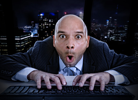 internet porn: young businessman late at night in office typing on computer keyboard with funny face expression on watching porn online and internet chat and social network addiction concept