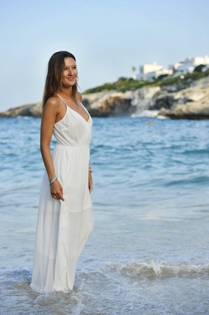letting: young attractive and beautiful woman enjoying vacation summer holidays at Spain coast village walking on beach sand letting white dress getting wet on sea water relaxed and happy