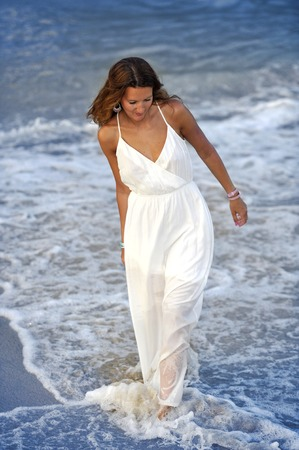 summer dress: young attractive and beautiful woman enjoying vacation summer holidays at Spain coast village walking on beach sand letting white dress getting wet on sea water relaxed and happy