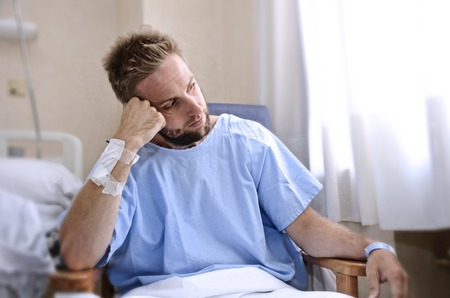 concerned: young injured man in hospital room sitting alone in pain looking negative and worried for his bad health condition sitting on chair suffering depression on a sad lonely medical background Stock Photo