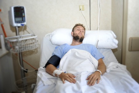 young injured patient man lying in bed hospital room resting from pain looking in bad health condition after suffering accident in health care concept
