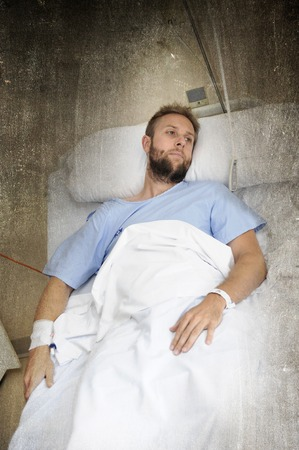 bad accident: young injured man lying in bed hospital room resting from pain worried about  bad health condition after suffering accident looking pensive sad and depressed in health care concept