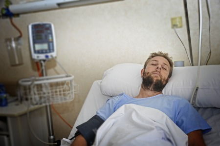 bad accident: young injured patient man lying in bed hospital room resting from pain looking in bad health condition after suffering accident in health care concept