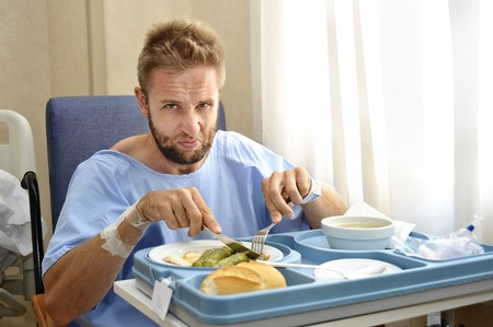 young man in hospital room after suffering accident eating the healthy diet clinic food in upset and moody face expression disliking the medical center meal Reklamní fotografie