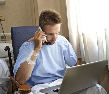 workaholic: young workaholic business man in hospital room sick and injured after accident working with mobile phone and computer laptop in health care and work obsession concept