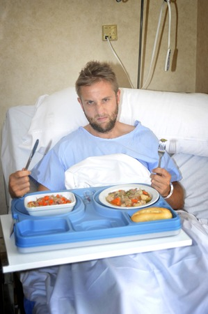 man sad: young man in hospital room after suffering accident eating healthy vegetables  as  diet clinic food in upset disgusting and moody face expression disliking the medical center meal