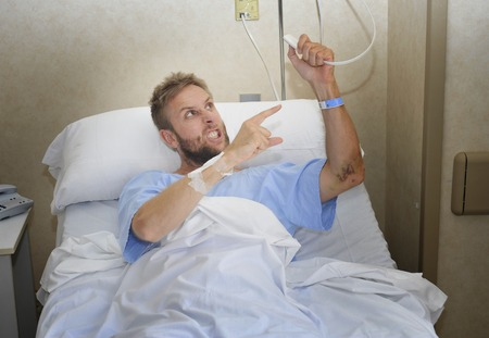 hospitalized: young angry patient man at hospital room lying in bed pressing nurse call button feeling nervous and upset in some kind of emergency health care and medical attention concept