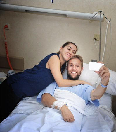 taking a wife: young happy couple in love taking selfie photo at hospital room with man ill lying in bed at clinic holding mobile phone shooting himself together with his wife or girlfriend in positive thinking concept Stock Photo
